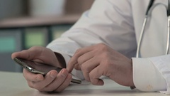 Physician's hands sliding files, typing text on smartphone, medical consulting Stock Footage