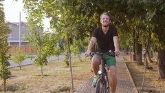 Handsome tall Caucasian male with light beard and black t-shirt riding bicycle Stock Footage