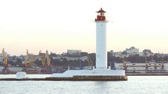View on white lighthouse and port from sea with city on background in slowmotion Stock Footage
