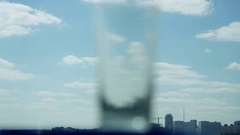 Empty glass on blurred blue sky and city background changes focus. 4k Stock Footage