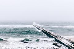 Sea view and a frozen pier in winter during a snowfall Stock Photos