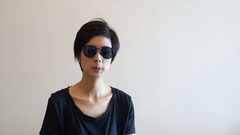 South East Asian girl wearing sunglasses moving her body along with songs Stock Footage