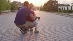 Young kid playing and his father playing with radio controlled car outside while Stock Footage
