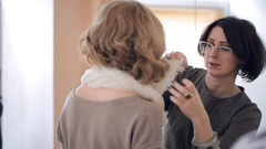 Woman showing how to tie a scarf around the neck of the model Stock Footage