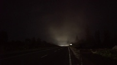Silhouettes of truck and car passing on road at night meet each other Stock Footage