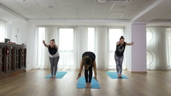 Teacher and two learners doing yoga sequence together during class Stock Footage