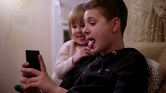 Little Sister and Elder Brother Having Fun With Mobile Phone and Making Funny Stock Footage