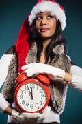Mixed race woman in santa hat with alarm clock. Stock Photos