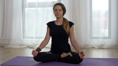 Woman meditating in lotus pose in a yoga studio Stock Footage