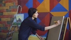 Young woman artist draw scetch wit pencil on easel canvas, preparing to paint Stock Footage