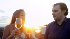 Young couple in love on romantic date at beach restaurant at sunset drinking Stock Footage