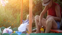 Grandma in hat and grandson playing in the sandbox, molded figurines from sand Stock Footage