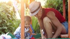 Fashionable grandma in hat and grandson playing in the sandbox, molded figurines Stock Footage