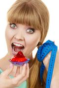 Woman holds cupcake trying to resist temptation Stock Photos