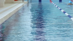 Young girl in goggles and cap swimming backstroke style in the blue water pool Stock Footage