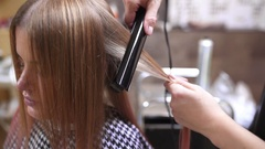 Barber makes curly hair for woman by hot curling, woman in the beauty studio Stock Footage