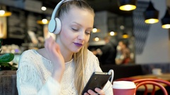 Girl wearing headphones and plays music on smartphone in the cafe, steadycam sho Stock Footage