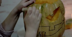 Girl Carves Details of a Jack o' Lantern on Orange Halloween Pumpkin Using a Stock Footage