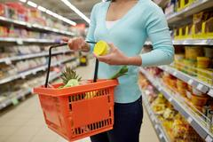 Woman with food basket and jar at grocery store Kuvituskuvat