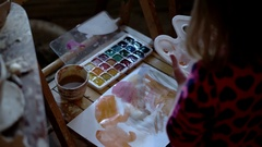 A Cute Little Girl Painting With Gouache Colors on on a White Sheet of Paper Stock Footage
