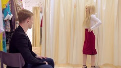 Sexy blonde with fun shows beautiful costume to her fiance in the dressing room Stock Footage