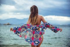 Beautiful young brunette woman in blue bikini posing on the beach in turning Stock Photos