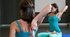 Woman doing yoga exercise in studio 4k video. Girl sits lotus asana stretching Stock Footage