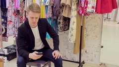 Handsome young man appreciates his girlfriend's new clothes in fitting room Stock Footage