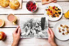 Hands holding picture of senior couple, breakfest meal. Studio s Kuvituskuvat