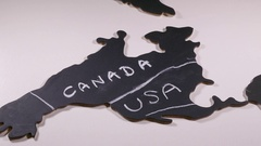 Hand chalking between boundary lines to name Canada on map cutout. Stock Footage