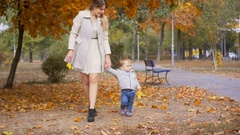 1 year old baby boy holding mother hand and walking on alley at park Stock Footage