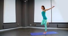 Woman doing yoga exercise 4k video. Girl stretching balancing posture Stock Footage
