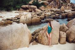 Beautiful young brunette woman in blue bikini posing on the beach. Sexy model Stock Photos