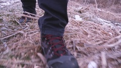 Man in hiking boots walking through countryside Stock Footage