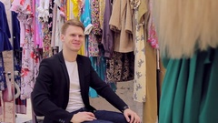 Attractive young man looking at his girlfriend a new dress in the dressing room Stock Footage