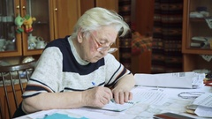 Elderly woman writing in journal, notebook, grandmother, 4k Stock Footage