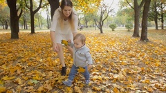 Slow motion footage of cute baby boy holding autumn leaves and walking with mom Stock Footage