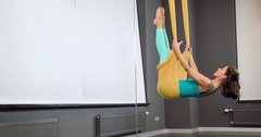 Woman doing aerial flow yoga exercise hammocks 4k video gravity fitness studio Stock Footage