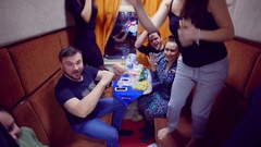 Cheerful group of friends go to relax on the train and incendiary dance in the Stock Footage