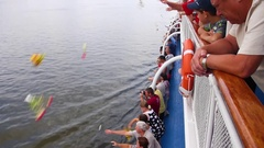 Passengers of the ship throw flowers into the river Volga Stock Footage
