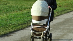 Unidentified woman with baby carriage approaching closeup Stock Footage