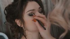 Makeup artist applies makeup a young woman before shooting Stock Footage