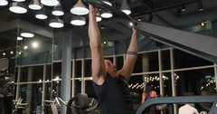 Man pulls weight exercise 4k gym video. Male training back muscles on machine Stock Footage