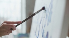 Female hand with a brush draws on a canvas, close-up Stock Footage