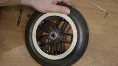 Man repairs wheel in pram Stock Footage