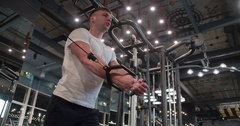 Man in gym doing pulls weight exercise 4k video. Chest training on machine Stock Footage
