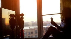 Beautiful young woman sitting on window uses smart phone taking picture and Stock Footage