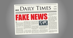 A mock-up newspaper spins into shot with FAKE NEWS Stock Footage