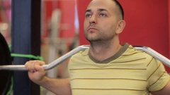 Squats in the gym. Paurlifting. Lifting. Squats with a weight. The man trains in Stock Footage