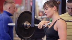 Squats in the gym. Paurlifting. Lifting. Squats with a weight. The woman trains Stock Footage